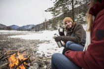 Couple on a trip in winter having a hot drink at camp fire — Stock Photo