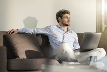 Man sitting on couch at home with laptop — Stock Photo