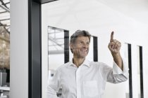 Sorridente uomo d'affari maturo toccando vetro pane in ufficio moderno — Foto stock