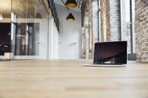 Ноутбук в коридоре современного офиса — стоковое фото