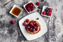Pancakes with red fruit jelly, maple sirup, raspberries and blueberries — Photo de stock