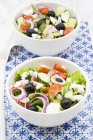 Deux cuvettes de salade grecque sur la table — Photo de stock