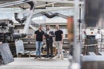 Трое мужчин стояли и разговаривали на заводе — стоковое фото
