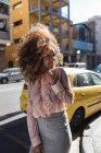 Портрет улыбающейся красивой молодой женщины с афро-прической в городе — стоковое фото