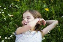 Портрет смеющейся маленькой девочки, лежащей на лугу — стоковое фото