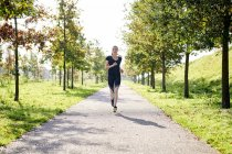 Young woman running in a park — Stock Photo