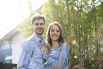 Portrait of smiling couple in garden in front of bamboo plants — Stock Photo