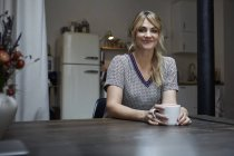 Portrait of smiling woman with cup of coffee sitting at table in kitchen — Stock Photo