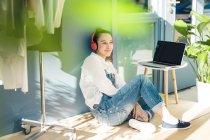 Смолящая молодая фрилансерша, сидящая на полу в своей студии, слушая музыку в наушниках и ноутбуке — стоковое фото