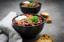 Bowl of Chili con Carne with fresh coriander and sour cream — Stock Photo