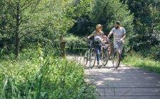 Famiglia che spinge biciclette su passerella in legno — Foto stock