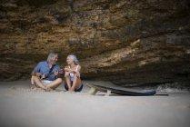Bella coppia anziana seduta sulla spiaggia, uomo che suona la chitarra — Foto stock