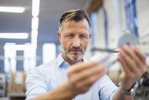 Reifer Geschäftsmann in Fabrik untersucht Bauteil — Stockfoto
