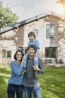 Portrait of happy family with son in garden of their home — Stock Photo