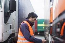 Man wearing reflective vest examining truck — Stock Photo