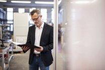 Зрілі бізнесмен в заводі дивлячись на папку — стокове фото
