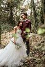 Наречений обіймаючи наречену з закритими очима в лісі — стокове фото