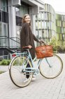 Donna sorridente con bicicletta in piedi di fronte a un edificio — Foto stock