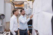 Deux hommes à l'usine regardant le plan — Photo de stock