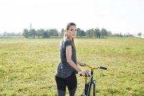 Jeune femme sportive avec le vélo sur un pré — Photo de stock