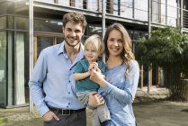 Портрет улыбающихся родителей с сыном перед их домом — стоковое фото