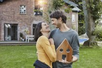 Happy couple in garden of their home holding house model — Stock Photo