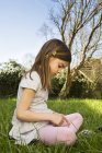 Little girl sitting on a meadow picking daisies — Stock Photo