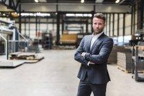 Портрет уверенного бизнесмена, стоящего на полу цеха — стоковое фото