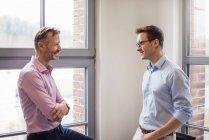 Dois empresários sorridentes a falar à janela — Fotografia de Stock