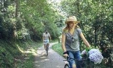 Coppia di biciclette a cavallo in una foresta — Foto stock