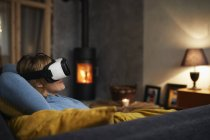Woman lying on couch and using Virtual Reality Glasses at home in evening — Stock Photo