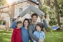 Портрет счастливой семьи в саду с крышей дома — стоковое фото