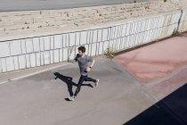 Un homme sportif qui court contre un mur — Photo de stock