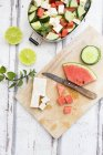Lunch box, preparation of watermelon salad with feta, cucumber, ment and lime dressing — стоковое фото
