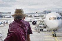 Мальчик в соломенной шляпе смотрит в окно самолета на фартуке — стоковое фото