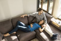 Affectionate couple relaxing on sofa at home — Stock Photo