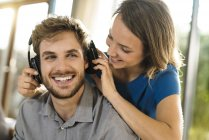 Smiling woman putting on headphones on boyfriend — Stock Photo