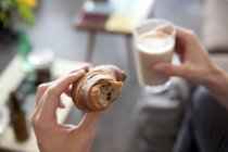 Man's hands holding croissant and  glass of Latte Macchiato — Stock Photo