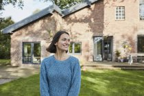 Smiling woman in garden of her home — Stock Photo