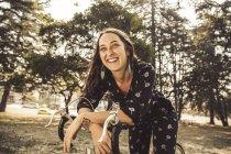 Счастливая молодая женщина с велосипедом в парке улыбается — стоковое фото