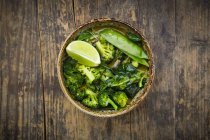 Bowl of green thai curry with broccoli, pak choi, snow peas, baby spinach and lime — стоковое фото