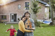 Portrait of smiling couple with daughter in garden of their home holding house model — Stock Photo