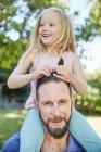 Ragazza felice seduta sulle spalle del padre e toccare i suoi capelli — Foto stock