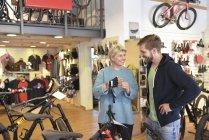 Продавец помогает клиенту в магазине велосипедов — стоковое фото