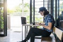 Artiste écrivant dans le cahier dans un café avec le café et l'ordinateur portatif sur la table — Photo de stock