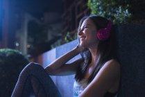 Mulher nova feliz com os auscultadores cor-de-rosa que escutam a música no ajuste urbano moderno na noite — Fotografia de Stock