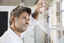 Retrato de homem de negócios maduro encostado à parede de vidro no escritório — Fotografia de Stock