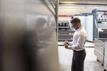 Empresário usando tablet no chão da fábrica — Fotografia de Stock