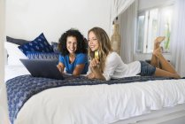 Two smiling women lying in bed shopping online with credit card and laptop — Stock Photo