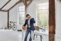 Empresário sorridente com basquete no celular na cobertura — Fotografia de Stock